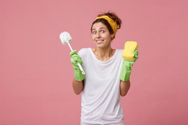 Młoda atrakcyjna gospodyni domowa w zwykłych ubraniach w rękawiczkach trzymająca spray do prania i szczotkę o zdziwionym spojrzeniu wzruszająca ramionami, patrząc ze zdumieniem na różową ścianę