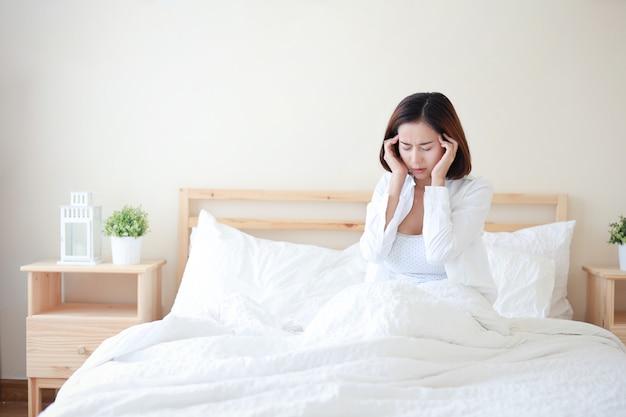 Młoda atrakcyjna i seksowna azjatycka kobieta ubrana w białą koszulę dostała bólu głowy na łóżku w białej sypialni z nieszczęśliwą twarzą.