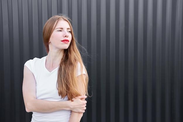 Młoda atrakcyjna imbirowa dziewczyna w białej koszula z czerwienią malował wargi pozuje na szarym metalowym panelu tle