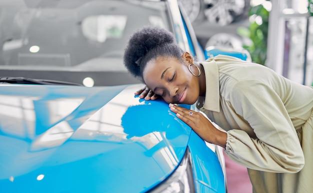 Młoda atrakcyjna kobieta afro cieszy się byciem właścicielem nowego samochodu