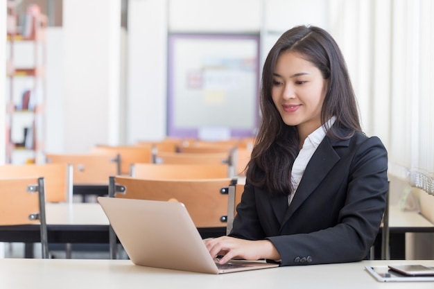 Młoda atrakcyjna kobieta azjatyckich biznesowych za pomocą laptopa siedzącego w biurze