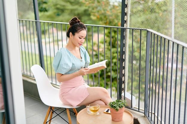 Młoda atrakcyjna kobieta azji czyta książkę na balkonie