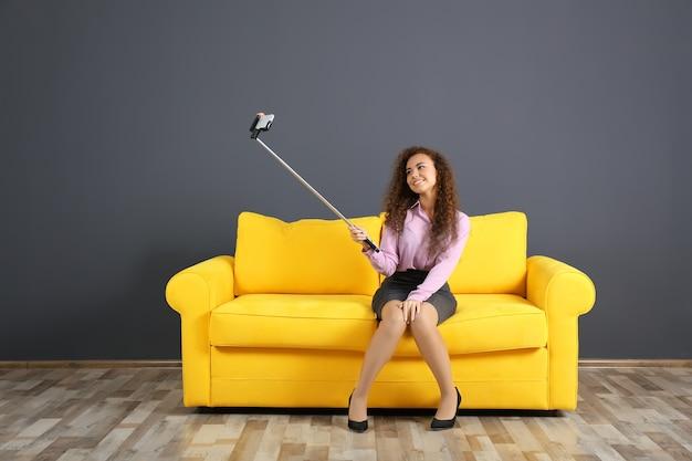 Młoda atrakcyjna kobieta biorąc selfie na żółtej kanapie w pokoju