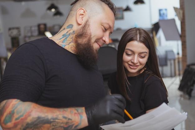 Młoda atrakcyjna kobieta coraz nowy tatuaż przez profesjonalnego tatuatora