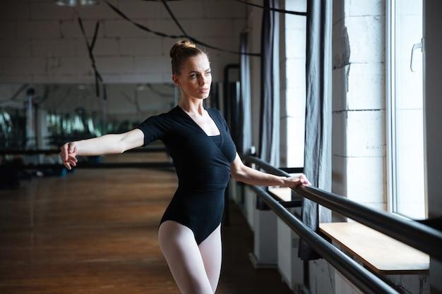 Młoda atrakcyjna kobieta ćwicząca w klasie baletowej