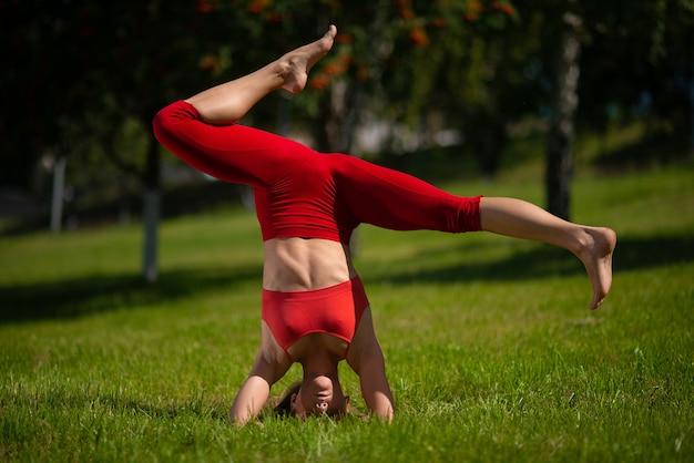 Młoda atrakcyjna kobieta ćwiczy joga outdoors. dziewczyna wykonuje handstand do góry nogami