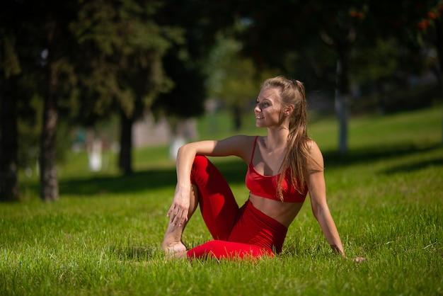 Młoda atrakcyjna kobieta ćwiczy joga outdoors. dziewczyna wykonuje różne ćwiczenia na trawie
