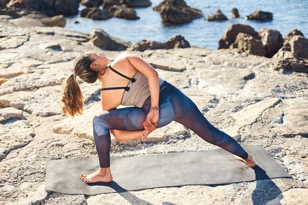 Młoda atrakcyjna kobieta ćwiczy jogę w pozie związanej kąt boku na plaży.