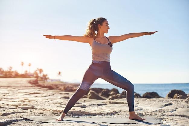 Młoda atrakcyjna kobieta ćwiczy jogę w pozycji wojownika na plaży.