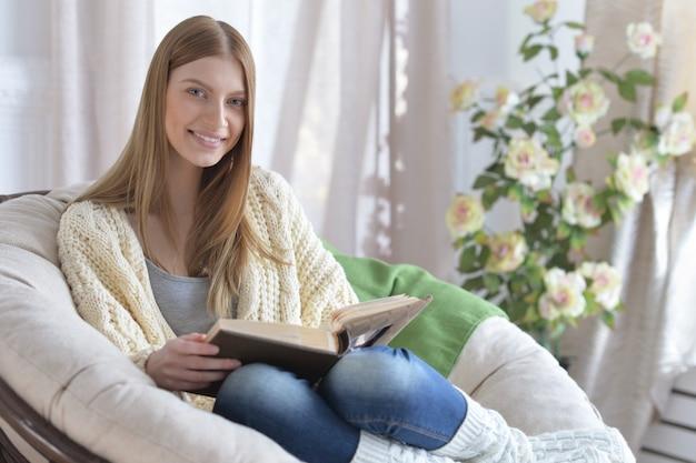 Młoda atrakcyjna kobieta czytająca książkę w wygodnym fotelu
