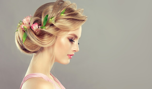 Młoda, atrakcyjna kobieta demonstruje blond włosy zebrane w elegancką fryzurę ze świeżymi kwiatami. sztuka fryzjerska, koloryzacja włosów i makijażu. portret z profilu.