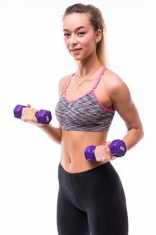 Młoda atrakcyjna kobieta dziewczyna fitness zrobić różne ćwiczenia aerobiku z hantlami na białym ubrana w sportową