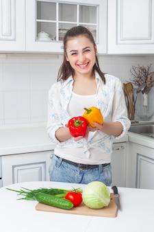 Młoda atrakcyjna kobieta gotowanie sałatki pomieszczeniu w kuchni