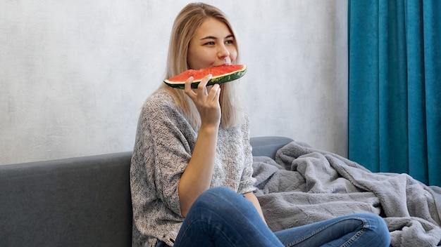 Młoda atrakcyjna kobieta gryzie kawałek arbuza. kobieta w domu w przytulnym wnętrzu