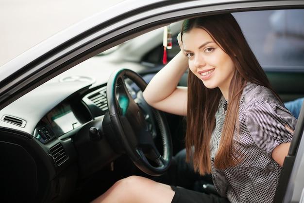 Młoda, atrakcyjna kobieta jedzie samochodem, wraca z pracy do domu