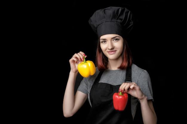 Młoda atrakcyjna kobieta kucharz w czarnym mundurze trzyma paprykę na czarnym tle