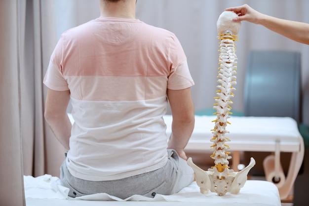 Młoda atrakcyjna kobieta lekarz posiadający model kręgosłupa i truing, aby zrozumieć, gdzie jest bolesne miejsce pacjenta.