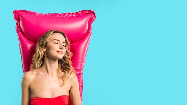 Młoda atrakcyjna kobieta leży na dmuchanym materacu