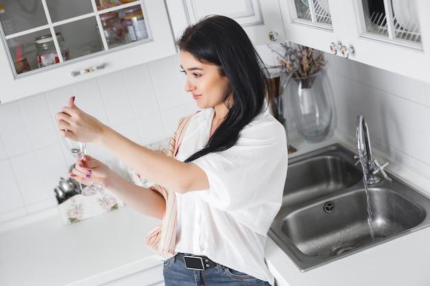 Młoda atrakcyjna kobieta myje szkło przy kuchnią. gospodyni myje naczynie w domu