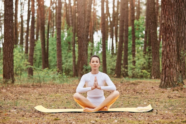 Młoda atrakcyjna kobieta nosi białą odzież sportową siedzącą na karemacie w pozycji lotosu