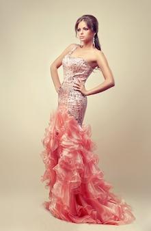 Młoda atrakcyjna kobieta o smukłej sylwetce ubrana jest w długą, srebrną suknię z różowymi koronkami, długie włosy zebrane w elegancką, swobodnie układającą się fryzurę. niebieskooki model z jasnym wieczorowym makijażem na twarzy.