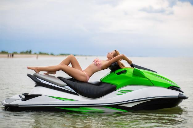 Młoda atrakcyjna kobieta o szczupłej sylwetce w stylowym stroju kąpielowym bikini bawi się na skuterze wodnym, letnie wakacje, aktywny sport