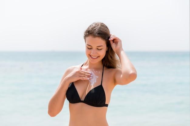 Młoda atrakcyjna kobieta ochrania skórę na piersi kremem z filtrem przeciwsłonecznym na słonecznej plaży.