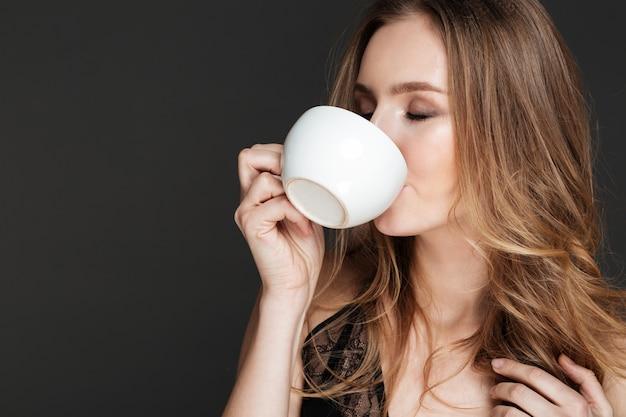 Młoda atrakcyjna kobieta pije kawę