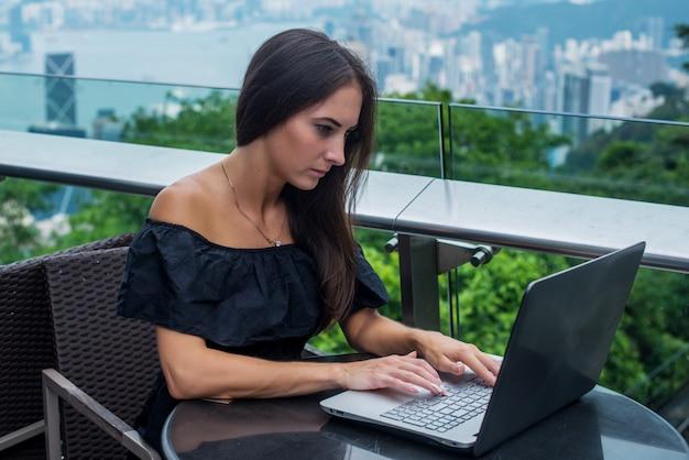 Młoda atrakcyjna kobieta pisania lub pracy na laptopie siedząc w kawiarni na dachu z widokiem na miasto.