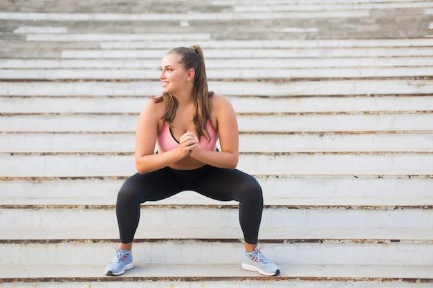 Młoda atrakcyjna kobieta plus size w sportowej bluzce i legginsach uprawia sport na schodach, radośnie patrząc na zewnątrz