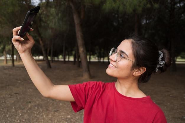 Młoda atrakcyjna kobieta po dwudziestce w okularach i czerwonej koszuli siedzi na ławce, trzymając telefon komórkowy i biorąc selfie, uśmiechając się w pięknym parku w hiszpanii. ona patrzy na telefon