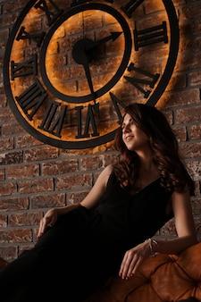Młoda atrakcyjna kobieta pod zegarem, na tle ściany z cegły - styl loft