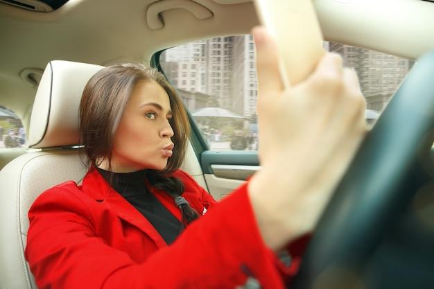 Młoda atrakcyjna kobieta podczas prowadzenia samochodu