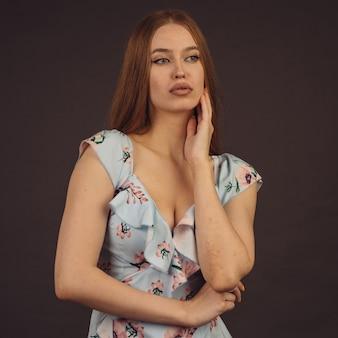 Młoda atrakcyjna kobieta pozuje w studio. dziewczyna z pełnymi ustami ma problemy ze skórą na twarzy i ciele, chorobę łuszczycy. nie traci serca i żyje pełnią życia, chce zostać modelką