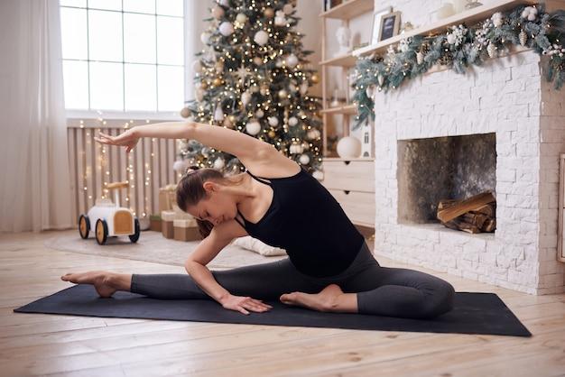 Młoda atrakcyjna kobieta praktykuje jogę w nowoczesnym domu