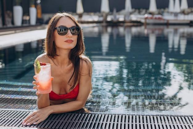 Młoda atrakcyjna kobieta przy basenie pijąca koktajl