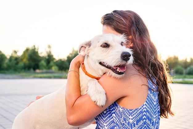 Młoda atrakcyjna kobieta przytulanie psa w parku