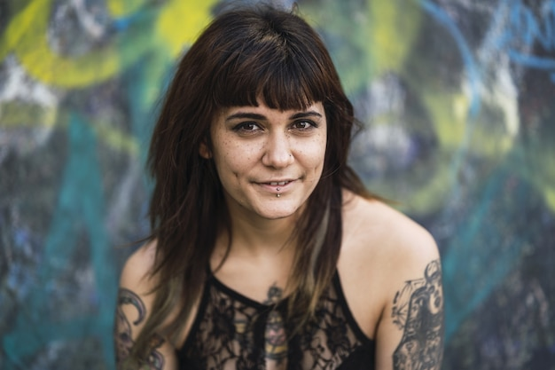 Młoda atrakcyjna kobieta rasy kaukaskiej z tatuażami siedzi na rampie