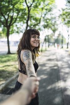 Młoda atrakcyjna kobieta rasy kaukaskiej z tatuażami stoi w parku i robi śliczną minę