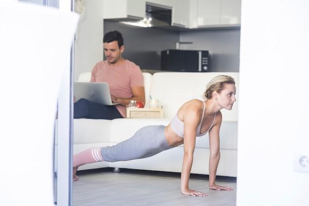 Młoda atrakcyjna kobieta robi ćwiczenia fitness i mężczyzna pracuje na kanapie z komputerem