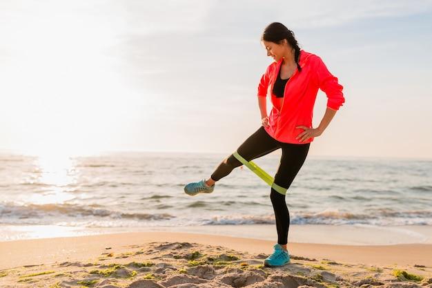 Młoda atrakcyjna kobieta robi ćwiczenia sportowe o porannym wschodzie słońca na plaży, zdrowy styl życia, słuchanie muzyki na słuchawkach, ubrana w różową wiatrówkę, rozciągająca się w gumce