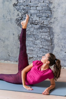 Młoda atrakcyjna kobieta robi nogi rozciągliwości ćwiczeniu