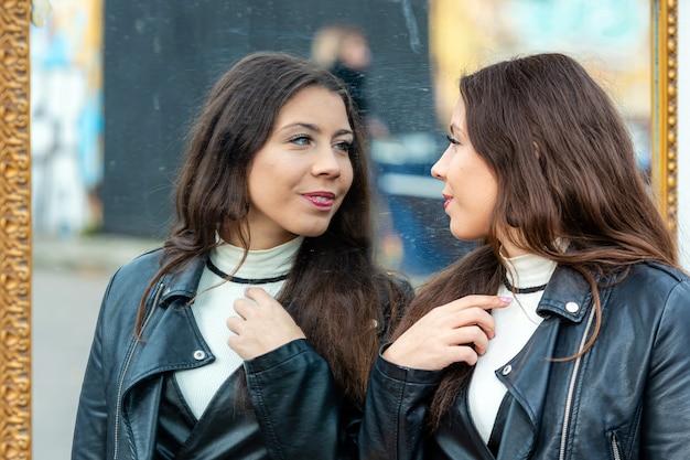 Młoda, atrakcyjna kobieta robi różne grymasy i cieszy się swoim odbiciem w lustrze
