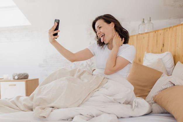 Młoda atrakcyjna kobieta robi selfie tuż po przebudzeniu