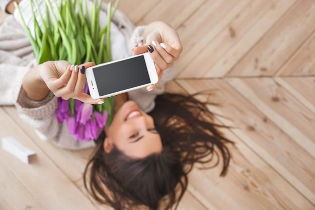 Młoda atrakcyjna kobieta robi selfie z kwiatami indoors