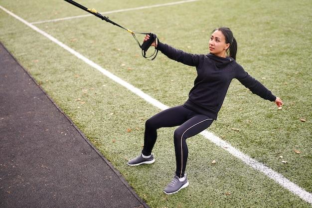 Młoda atrakcyjna kobieta robi trening zawieszenia z paskami fitness na świeżym powietrzu
