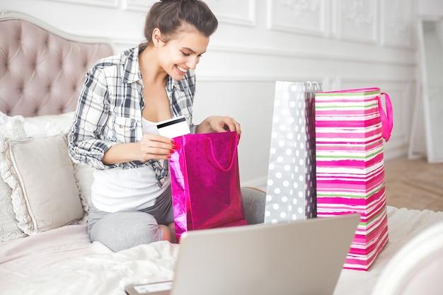 Młoda atrakcyjna kobieta robi zakupy online w domu