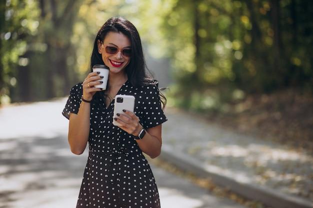 Młoda atrakcyjna kobieta rozmawia przez telefon w parku