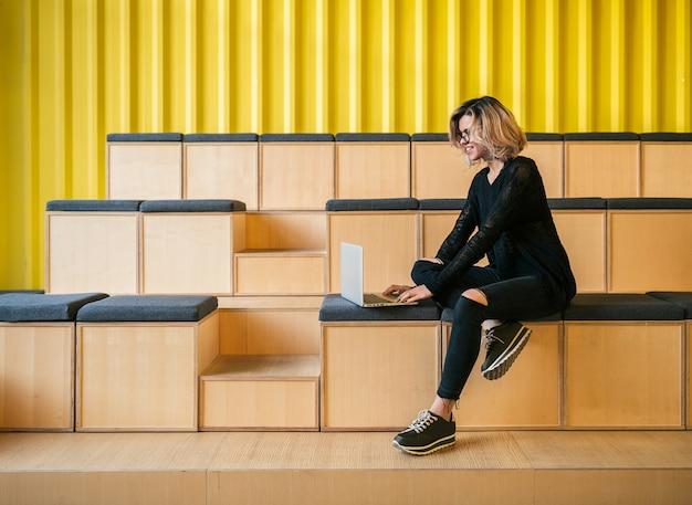 Młoda atrakcyjna kobieta siedząca w sali wykładowej, pracująca na laptopie, w okularach, nowoczesne audytorium, edukacja studencka online, freelancer, uśmiechnięta, nastoletni startup