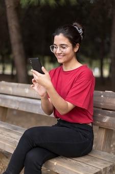 Młoda atrakcyjna kobieta siedzi na ławce i używa jej telefon w parku z szkłami, z czerwoną koszula. sewilla, hiszpania